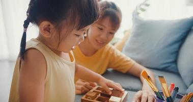 feliz alegre mãe de família asiática ensinar menina jogar passatempo de jogo de tabuleiro com caixa de madeira se divertindo, relaxar no sofá na sala de estar em casa. passar um tempo juntos, distância social, quarentena para coronavírus. foto