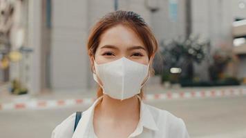 bem sucedida jovem empresária asiática em roupas de escritório de moda usar máscara médica sorrindo e olhando para a câmera enquanto feliz sozinho ao ar livre na cidade moderna urbana. conceito de negócios em movimento. foto