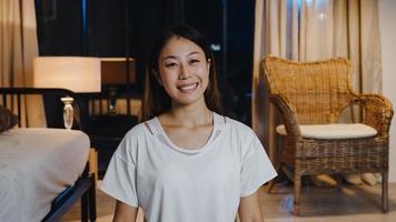 alegre jovem asiática se sentindo feliz sorrir e olhar para a câmera usando o telefone para fazer videochamada ao vivo na sala de estar em casa à noite. distanciamento social, quarentena para coronavírus. close-up visualização da webcam. foto