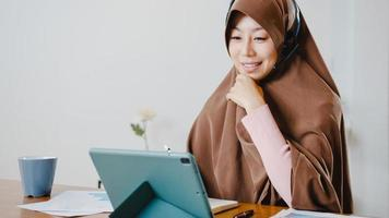 A senhora muçulmana asiática usa fone de ouvido usando tablet digital e fala com colegas sobre o relatório de venda em videoconferência enquanto trabalha em casa na cozinha. distanciamento social, quarentena para o vírus corona. foto