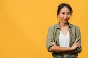 retrato de jovem asiática com expressão positiva, braços cruzados, sorriso largo, vestido com roupas casuais e olhando para a câmera sobre fundo amarelo. feliz adorável feliz mulher alegra sucesso. foto