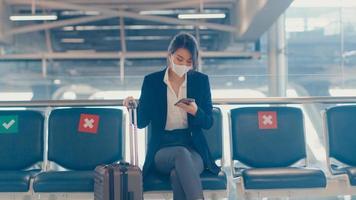 O viajante asiático da senhora de negócios usa terno sentado com a mala e usa a mensagem de bate-papo do telefone inteligente no banco, espera o voo no aeroporto. viajante de negócios em uma pandemia covid, conceito de viagens de negócios. foto