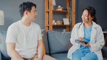 jovem asiática médica médica usando tablet digital, compartilhando boas notícias de testes de saúde com paciente feliz do sexo masculino, sentado no sofá em casa. seguro médico, visite o conceito de paciente em casa. foto