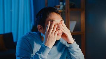 ásia empresário faça uma pausa trabalho duro se sinta cansado relaxe os olhos após foco muito tempo tipo computador na sala de estar em casa horas extras à noite, síndrome do escritório, trabalho em casa conceito de pandemia de corona. foto