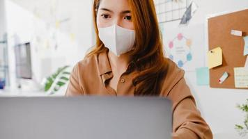 Ásia empresária usa máscara para distanciamento social em uma nova situação normal para prevenção de vírus enquanto usa laptop para apresentar a colegas sobre plano em videochamada enquanto trabalha no escritório. foto