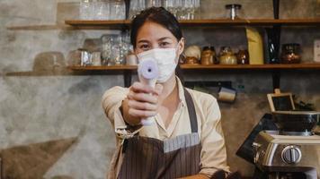 jovem funcionária do restaurante asiático usando máscara protetora usando o verificador de termômetro infravermelho ou pistola de temperatura na testa do cliente antes de entrar. estilo de vida novo normal após o vírus corona. foto