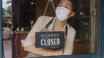 jovem asiática usa máscara facial virando uma placa de aberta para fechada na porta de vidro do café após a quarentena de bloqueio de coronavírus. proprietário de uma pequena empresa, comida e bebida, conceito de crise financeira empresarial foto
