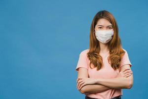jovem asiática usando máscara médica com os braços cruzados, vestida com um pano casual e olhando para a câmera isolada sobre fundo azul. auto-isolamento, distanciamento social, quarentena para o vírus corona. foto