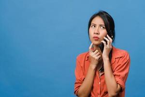 jovem asiática falar por telefone com expressão negativa, gritar animado, chorar com raiva emocional em um pano casual e ficar isolado em um fundo azul com espaço de cópia em branco. conceito de expressão facial. foto