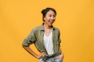 retrato de jovem asiática com expressão positiva, sorriso amplo, vestido com roupas casuais sobre fundo amarelo. feliz adorável feliz mulher alegra sucesso. conceito de expressão facial. foto