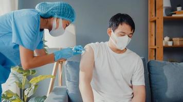 jovem enfermeira asiática dando vacina antivírus covid-19 ou gripe a um paciente do sexo masculino com máscara facial de proteção contra doenças virais, sentada no sofá da sala de estar em casa. conceito de vacinação. foto