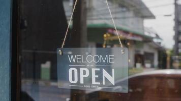 Bem-vindo, estamos abertos com um letreiro retro preto e branco vintage em um café com porta de vidro após a quarentena de bloqueio de coronavírus. proprietário de uma pequena empresa, comida e bebida, conceito de reabertura de negócios. foto
