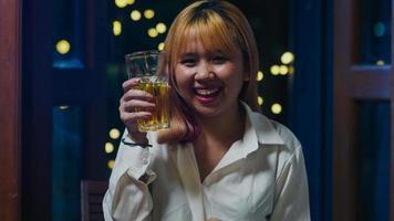 jovem asiática bebendo cerveja se divertindo feliz noite festa ano novo evento on-line celebração via videochamada por telefone em casa à noite. distância social, quarentena para coronavírus. ponto de vista ou pov foto