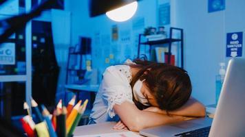 freelance asiática exausta senhora usar máscara facial dormindo no novo escritório em casa normal. trabalhando em casa sobrecarregada à noite, remotamente, auto-isolamento, distância social, quarentena para prevenção do vírus corona foto