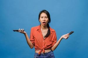 jovem asiática usando telefone e cartão de crédito com expressão negativa, animado gritando, choro com raiva emocional em um pano casual e ficar isolado sobre fundo azul. conceito de expressão facial. foto