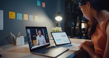 mulher asiática usando laptop ver gráfico na mesa de conversa com colegas sobre o trabalho em videochamada enquanto trabalhava em casa na sala de estar à noite. auto-isolamento, distanciamento social, quarentena para coronavírus. foto