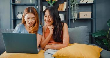 duas mulheres lésbicas da Ásia site juntos no sofá, olhando para a tela do laptop na sala de estar em casa juntos. senhoras de companheiro de quarto de casal feliz desfrutar de compras on-line de navegação na web, conceito de mulher de estilo de vida em casa. foto