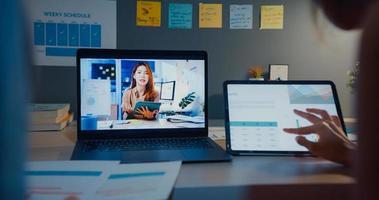 Senhoras de jovem estudante financeiro da Ásia assistindo aula on-line e estudando com laptop e tablet na sala de estar em casa à noite. tomando notas enquanto olha para a tela do computador, aprenda o conceito online. foto