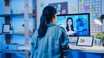 empresária asiática usando desktop conversa com colegas sobre o plano de uma reunião de videochamada na sala de estar. trabalho em casa sobrecarregada à noite, trabalho remoto, distanciamento social, quarentena para coronavírus. foto