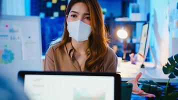 empresários asiáticos usando laptop apresentação e reunião de comunicação para brainstorming de idéias sobre novos colegas de projeto que trabalham plano de estratégia de sucesso usam máscara facial de volta no novo escritório noturno normal. foto