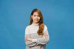 retrato de jovem asiática com expressão positiva, braços cruzados, sorriso largo, vestido com roupas casuais e olhando para a câmera sobre fundo azul. feliz adorável feliz mulher alegra sucesso. foto
