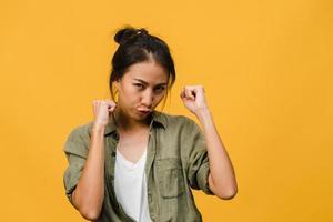 jovem asiática com expressão positiva, alegre e emocionante, vestida com um pano casual e olha para a câmera sobre fundo amarelo. feliz adorável feliz mulher alegra sucesso. conceito de expressão facial. foto