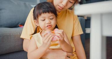 feliz alegre família asiática mãe e criança menina comendo donuts e se divertindo, relaxar desfrutar no sofá na sala de estar em casa. passar um tempo juntos, distância social, quarentena para coronavírus. foto