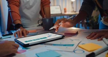 close-up asiáticos empresários reunindo plano de análise estatísticas brainstorm e cabeçalho da equipe seguram tablet gráfico gráfico ponto e funcionário tomam nota na noite do escritório em casa. conceito de sucesso de estratégia de finanças. foto