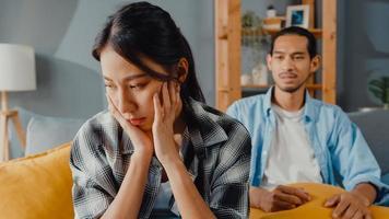 esposa de casal asiático chateado sentar no sofá ouvir marido furioso gritando, sentir infeliz conversa negativa com ela. casal tem briga ou desentendimento em casa, problema de casal, relacionamento tóxico com família e casamento. foto