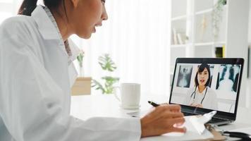 jovem doutora da Ásia em uniforme médico branco usando laptop falando videoconferência com médico sênior na mesa na clínica de saúde ou hospital. distanciamento social, quarentena para o vírus corona. foto
