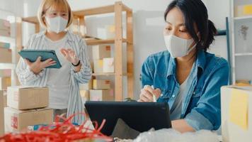 jovens mulheres de negócios asiáticas usam máscara facial verificar o pedido de compra do produto no estoque e salvar no computador tablet para trabalhar no escritório doméstico. proprietário de uma pequena empresa, entrega de mercado online, conceito freelance de estilo de vida foto