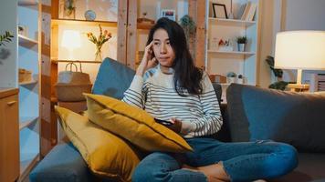 senhora asiática, pensativa, segurando o telefone, sentindo-se triste à espera de uma ligação, sente-se no sofá na sala de estar à noite em casa, sinta-se solitária, triste adolescente deprimido passar um tempo sozinho, distância social, quarentena de coronavírus. foto