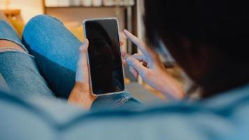 jovem asiática usar telefone inteligente com simulação de tela preta em branco para texto de publicidade, enquanto descansa no sofá na sala de estar em casa à noite moderna. tecnologia chroma key, conceito de design de marketing. foto
