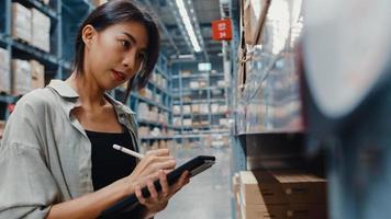 atraente jovem gerente de empresária da Ásia à procura de mercadorias usando tablet digital, verificando os níveis de estoque em um shopping center de varejo. distribuição, logística, embalagens prontas para embarque. foto
