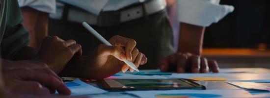 empresários e empresárias da ásia encontrando-se com ideias para brainstorming, colegas que trabalham juntos, planejando uma estratégia de sucesso, desfrutam do trabalho em equipe no escritório noturno. fundo de banner panorâmico com espaço de cópia. foto