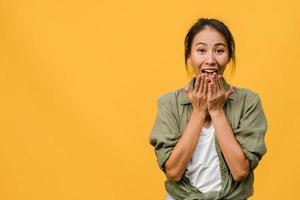 jovem asiática sente felicidade com uma expressão positiva, alegre surpresa funky, vestida com um pano casual e olhando para a câmera isolada em fundo amarelo. feliz adorável feliz mulher alegra sucesso. foto