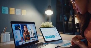 mulher asiática usando laptop fala com colegas sobre o trabalho em uma videochamada enquanto trabalhava em casa na sala de estar à noite. auto-isolamento, distanciamento social, quarentena para prevenção do coronavírus. foto