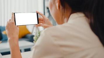 jovem asiática usar telefone inteligente com simulação de tela branca em branco para texto de publicidade enquanto inteligente trabalhando em casa na sala de estar. tecnologia chroma key, conceito de design de marketing. foto
