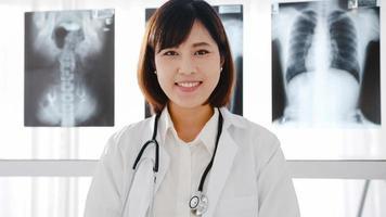 confiante jovem médica asiática em uniforme médico branco com estetoscópio, olhando para a câmera e sorrindo durante a videoconferência com o paciente no hospital de saúde. consultoria e conceito de terapia. foto