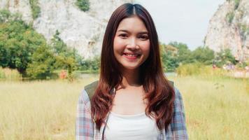 alegre jovem viajante asiática com mochila, sentindo-se feliz, sorrindo para a câmera no lago de montanha. menina coreana Aproveite sua aventura de férias sentindo liberdade feliz. viagens de estilo de vida e conceito de relaxamento. foto