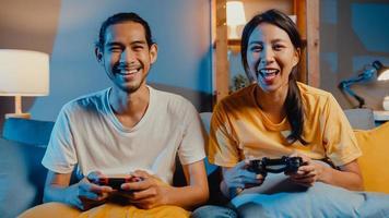 feliz ásia jovem casal homem e mulher se sentam no sofá, usam o controlador do joystick para jogar videogame, passar momentos divertidos juntos na sala de estar à noite. estilo de vida familiar de casal asiático, conceito de ficar em casa. foto