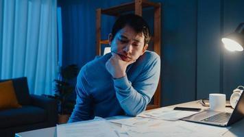 empresário freelance asiático foco tipo de trabalho no computador portátil ocupado com gráfico cheio de papelada na mesa na sala de estar em casa horas extras à noite, trabalhar em casa durante o conceito de pandemia covid-19. foto