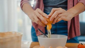 mãos do jovem chef asiático quebrando ovos em uma tigela de cerâmica, cozinhando omelete com legumes na placa de madeira na mesa da cozinha em casa. estilo de vida saudável comer e conceito tradicional de padaria. foto