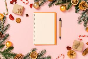 mínima criativa plana lay de composição tradicional de natal de inverno e temporada de férias de ano novo. vista superior caderno preto de maquete aberta para texto em fundo rosa. mock up e cópia da fotografia do espaço. foto