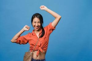 jovem senhora asiática com expressão positiva, alegre e emocionante, vestida com um pano casual e olha para a câmera sobre fundo azul. feliz adorável feliz mulher alegra sucesso. conceito de expressão facial. foto