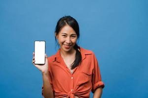 jovem asiática mostra tela vazia do smartphone com expressão positiva, sorri amplamente, vestida com roupas casuais, sentindo felicidade sobre fundo azul. telefone celular com tela branca na mão feminina. foto