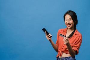 jovem asiática usando telefone e cartão de crédito com expressão positiva, sorri amplamente, vestida com roupas casuais e carrinho isolado sobre fundo azul. feliz adorável feliz mulher alegra sucesso. foto