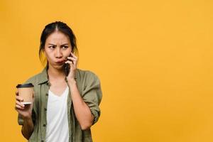 jovem asiática falar por telefone e segurar a xícara de café com expressão negativa, gritando animado, chorar com raiva emocional em um pano casual e ficar isolado no fundo amarelo. conceito de expressão facial. foto