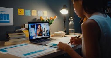 empresária asiática usando laptop conversa com colegas sobre o plano de uma reunião de videochamada na sala de estar em casa. trabalho em casa sobrecarregada à noite, remotamente, distância social, quarentena para coronavírus. foto