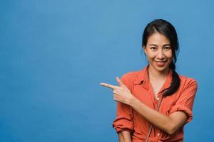 retrato de uma jovem asiática sorrindo com uma expressão alegre, mostra algo incrível no espaço em branco em um pano casual e olhando para a câmera isolada sobre fundo azul. conceito de expressão facial. foto